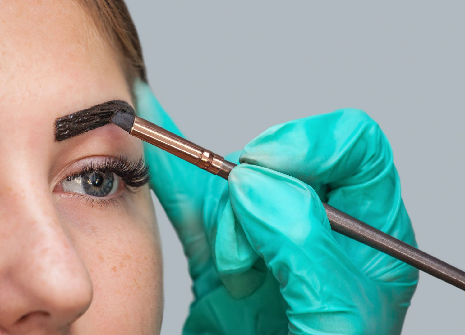 Clinician applies paint henna on brow